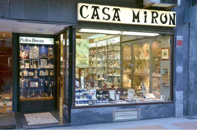 La imagen muestra la tienda casa mirón por fuera, donde aparece un cartel con el nombre en grande. Se pueden ver varios productos como copas y marcos de fotos.